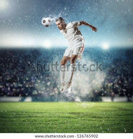 football player in white shirt striking the ball at the stadium - stock photo
