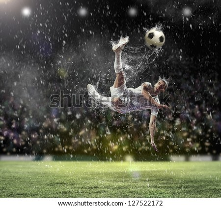football player in white shirt striking the ball at the stadium under the rain - stock photo