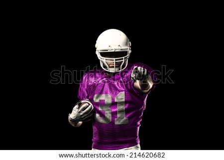 Football Player on a pink uniform celebrating on a black background.