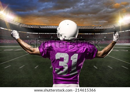 Football Player on a pink uniform celebrating on a stadium background.