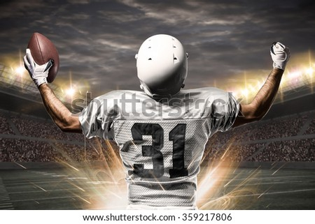 Football Player on a white uniform celebrating on a Stadium. - stock photo