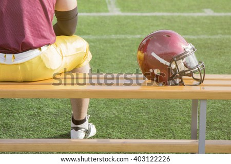 Football player sitting on a bench and sports helmet