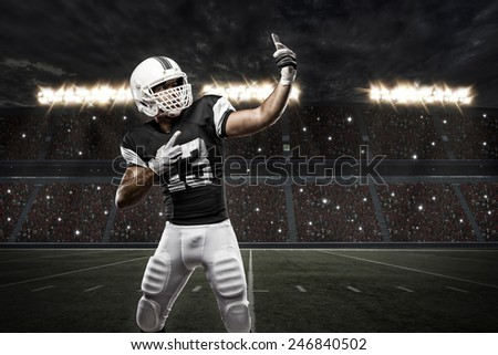 Football Player with a Black uniform making a selfie on a stadium. - stock photo