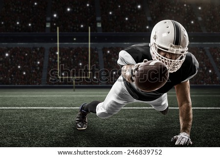 Football Player with a Black uniform scoring on a Stadium. - stock photo