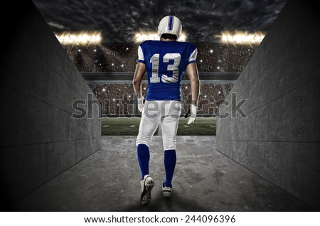 Football Player with a blue uniform walking out of a Stadium tunnel. - stock photo