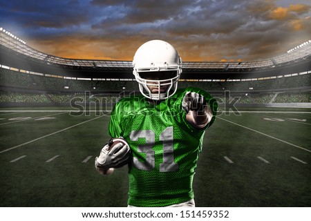 Football Player with a green uniform celebrating with the fans. - stock photo