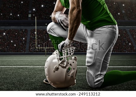 Football Player with a green uniform on his knees, on a Stadium. - stock photo