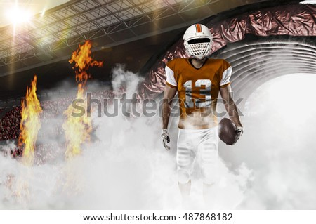 Football Player with a orange uniform coming out of a stadium tunnel.