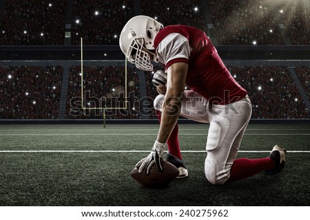 Football Player with a red uniform on his knees, on a Stadium. - stock photo