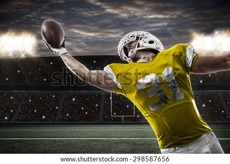 Football Player with a yellow uniform catching a ball on a stadium. - stock photo