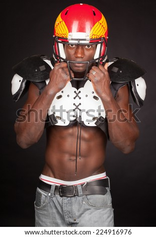 Football Player with American Football Shoulder and helmet - stock photo