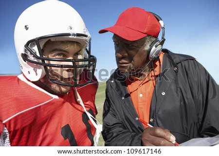 Football player with an African American coach - stock photo