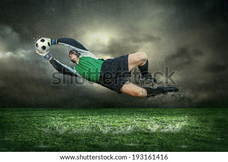 Football player with ball in action under rain outdoors - stock photo