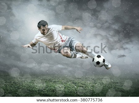 Football player with ball in action under sky with clouds - stock photo