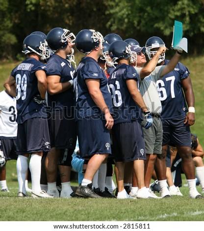 Football players around their coach. - stock photo
