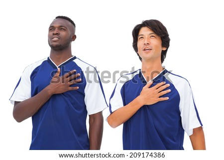Football players in blue with hands on heart on white background - stock photo