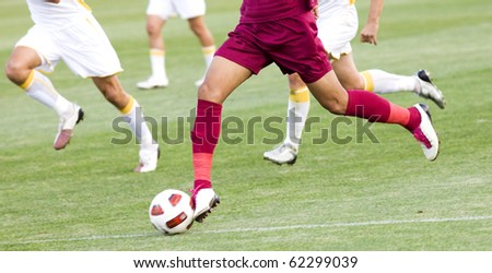 Football players running for the ball - stock photo