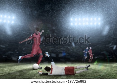 Football players tackling for the ball against football pitch under spotlights