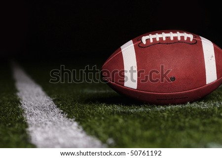 Football resting on the first down line - stock photo
