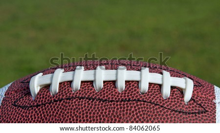 Football sitting on a grass background - stock photo