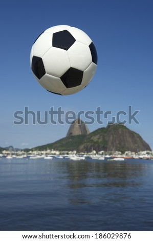 Football soccer ball flying in the sun above Botafogo Bay Rio de Janeiro with Sugarloaf Mountain in the background Brazil - stock photo