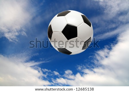 football soccer ball under blue sky with clouds