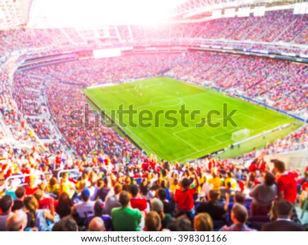 Football- soccer fans cheer their team and celebrate goal in full stadium with open air  with bright lighting beam     -blurred picture. - stock photo