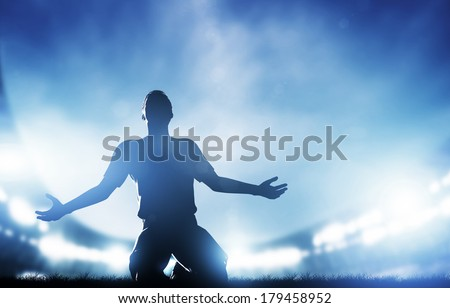 Football, soccer match. A player celebrating goal, victory. Lights on the stadium at night. - stock photo