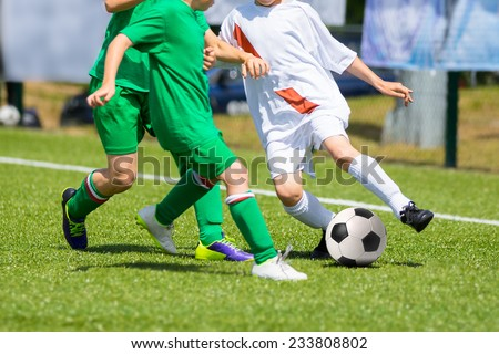 Football soccer match for children. Boys playing football game on a school tournament. Dynamic, action picture of kids competition during playing football. Sport background image. - stock photo