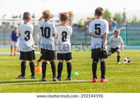 Football soccer match for children. Kids waiting on a bench. - stock photo