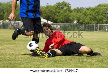 Football - Soccer player making sliding tackle