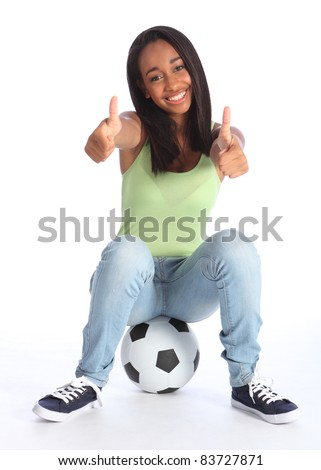 Football sports success for beautiful young African American teenage school girl soccer player, sitting on a ball with thumbs up sign. Wearing blue jeans and casual vest and has a big happy smile. - stock photo