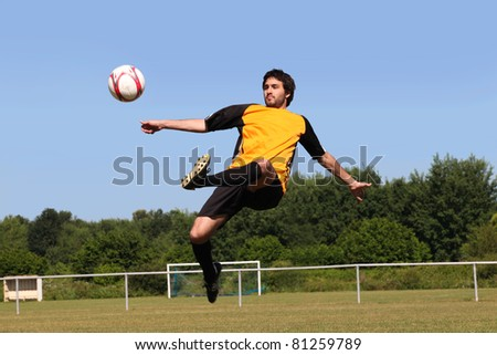 Footballer kicking the ball in mid air - stock photo