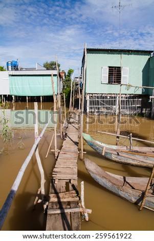 Footbridge and houses built on stilts on the Mekong Delta, Vietnam. - stock photo