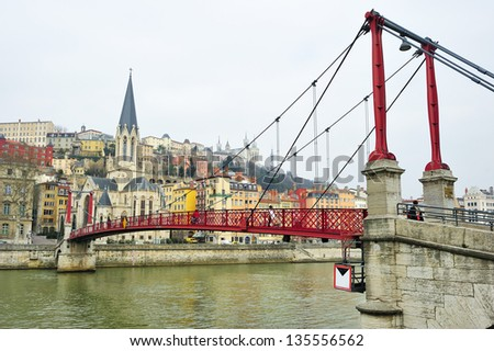 footbridge on Saone river that leads to the church of St. George - stock photo