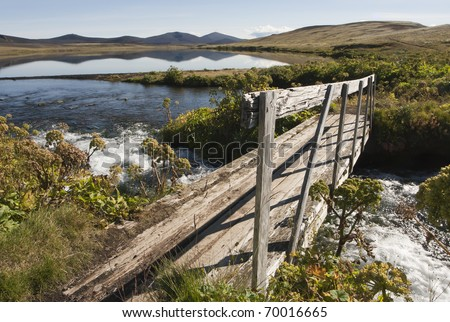 Footbridge over a small lake in Iceland - stock photo