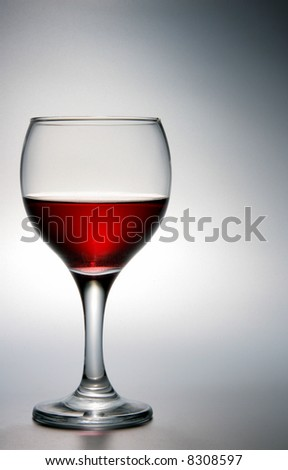 Footed glass of red wine over grey background