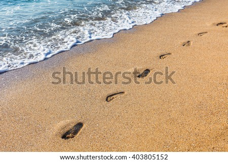 Footmarks on the sandy beach with soft wave of the sea - stock photo