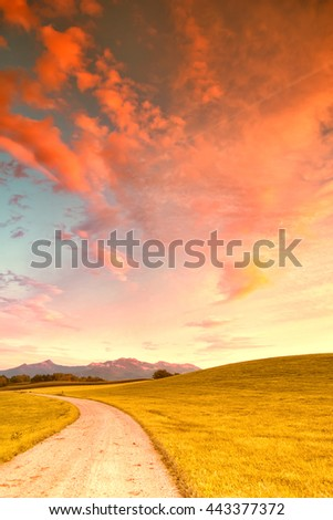 footpath and meadow with mountain kampenwand, evening sky - stock photo