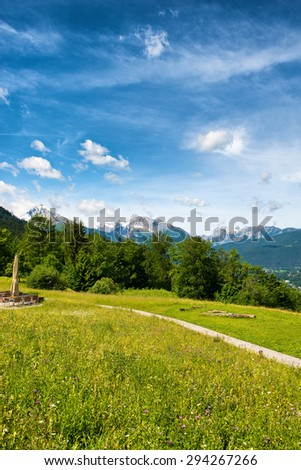 Footpath in the Berchtesgaden Alps in Germany crossing a lush green grassy plateau with a view to distant mountain peaks - stock photo
