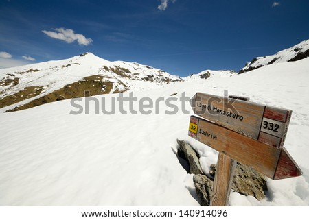 Footpath's wooden signposts in scenic snowy mountain landscape. Location: western Alps, Piedmont, Italy. - stock photo