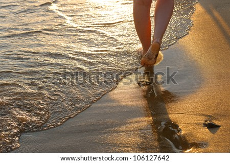 footprint on sand. Sunset illumination, a fragment of female feet - stock photo