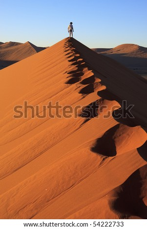 Footprints and man looking at the view at the top of a dune - stock photo