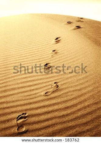 Footprints going over a sand dune. - stock photo