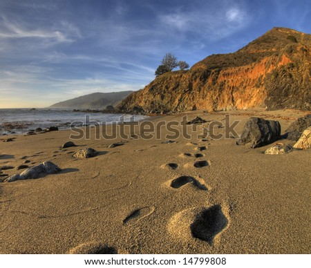Footprints heading off into the distance on the beach at Big Sur, California with the water, cliffs and a beautiful sky in the background - stock photo