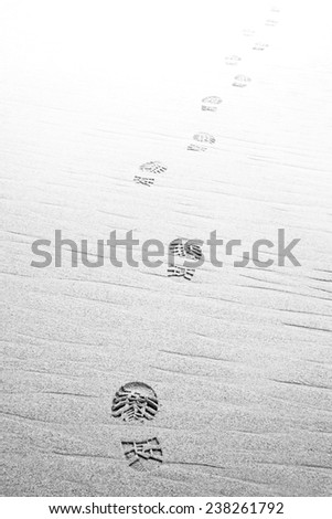 Footprints hiking boots on beach ,fading to white. Monochrome - stock photo