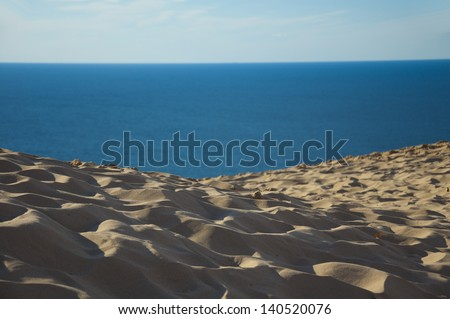 Footprints in sand by water - stock photo