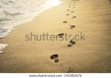 Footprints in the sand at sunset - stock photo