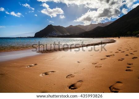 footprints in the sand at the beach Las Teresitas on the sunset, Tenerife island, Spain - stock photo
