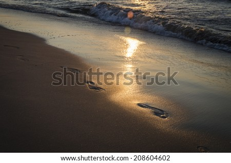 footprints in the sand, in the light of the setting sun - stock photo